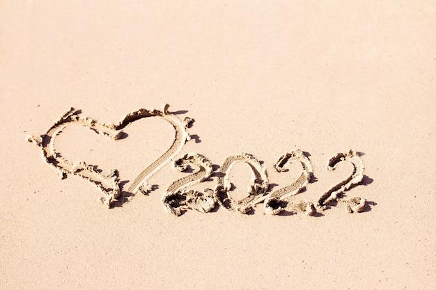 Die inschrift und das herz sind auf das neujahrssymbol aus hellem sand gezeichnet