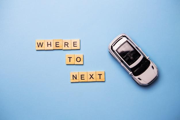 Die inschrift wo zu nächsten holzbuchstaben an einer blauen wand eine draufsicht. auto travel mit einem weißen auto am straßenrand.