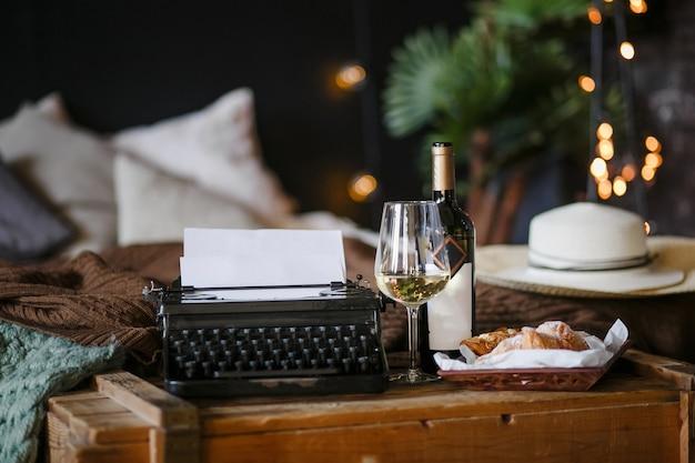 Die inspiration eines schriftstellers, der texte auf einer vintage-schreibmaschine freelancer frühstückscroissants und weinbüro im loft-stil tippt