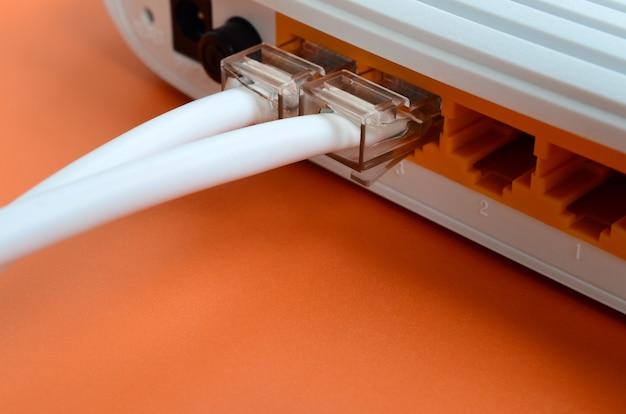 Die internet-kabelstecker sind mit dem internet-router verbunden, der auf einem orangefarbenen hintergrund liegt