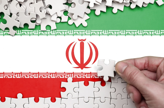Die iran-flagge ist auf einem tisch abgebildet, auf dem die menschliche hand ein puzzle weißer farbe faltet