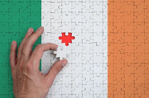 Die irland-flagge ist auf einem puzzle abgebildet, das mit der hand des mannes gefaltet wird