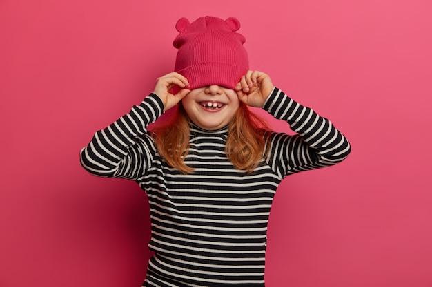 Die isolierte aufnahme eines hübschen vierjährigen mädchens trägt einen gestreiften pullover und einen rosa hut, hat spaß und deckt die augen ab, genießt es, zeit im familienkreis zu verbringen, isoliert auf der rosa wand. kinder, gefühle, kleidung