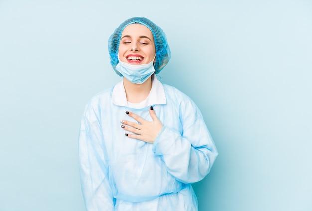 Die isolierte junge chirurgin lacht laut und hält die hand auf der brust.