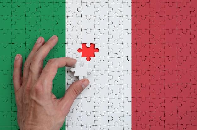 Die italienische flagge ist auf einem puzzle abgebildet, das mit der hand des mannes gefaltet wird