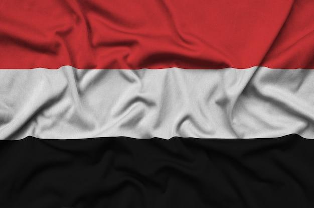 Die jemenitische flagge ist auf einem sportstoff mit vielen falten abgebildet.