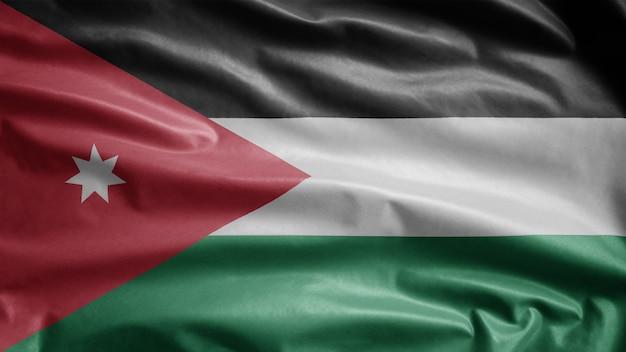 Die jordanische flagge weht im wind. nahaufnahme von jordania banner weht, weiche und glatte seide. stoff textur fähnrich hintergrund. verwenden sie es für das konzept für nationalfeiertage und länderanlässe.