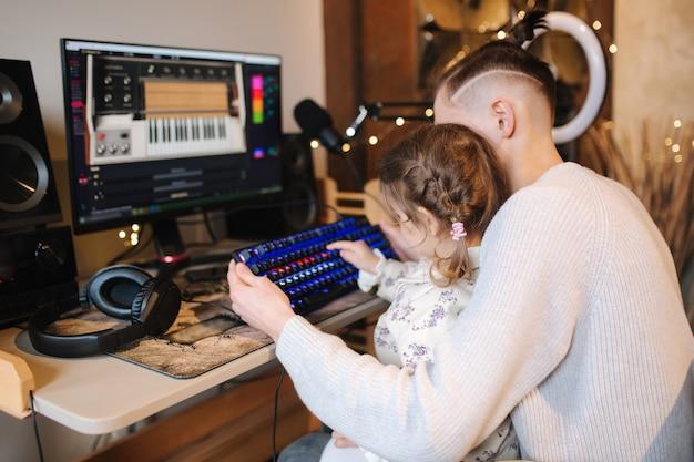 Die jüngere schwester sitzt auf den knien der brüder und legt mit hilfe eines neonleichten kleinen mädchens den finger auf die tastatur