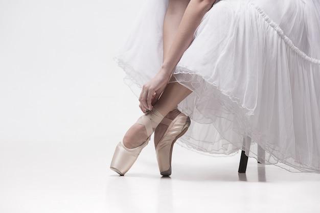 Die jugendlich ballerina in der weißen packung sitzt auf stuhl