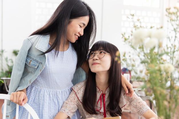 Die jugendlich liebe mit zwei asiatischen mädchen betrachten zusammen einander freundschaft oder lesbisches konzept.