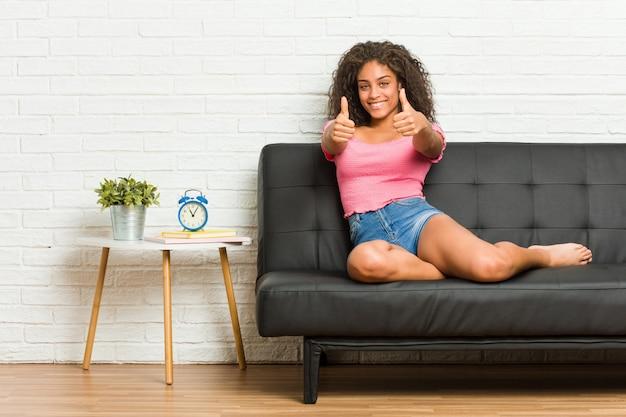 Die junge afroamerikanerfrau, die auf dem sofa mit den daumen sitzt, ups, beifall über etwas, unterstützung und respektkonzept.