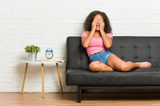 Die junge afroamerikanerfrau, die auf dem sofa sitzt, bedeckt augen mit den händen und lächelt breit, auf eine überraschung wartend.