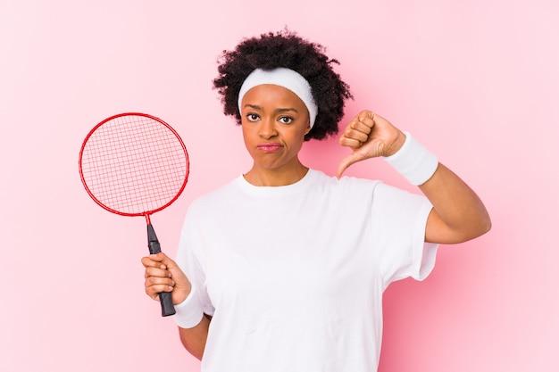 Die junge afroamerikanerfrau, die badminton spielt, lokalisierte das zeigen einer abneigungsgeste, daumen unten. uneinigkeit konzept.