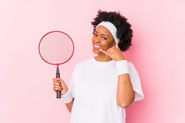 Die junge afroamerikanerfrau, die badminton spielt, lokalisierte das zeigen einer handyanrufgeste mit den fingern.