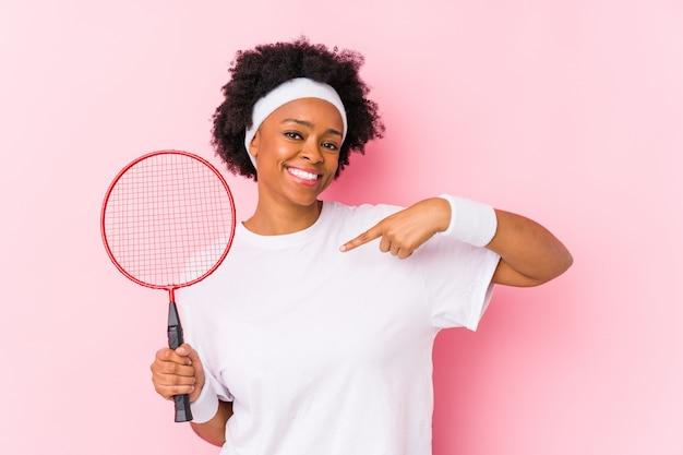 Die junge afroamerikanerfrau, die badminton spielt, lokalisierte die person, die eigenhändig auf einen hemdkopienraum zeigt, stolz und überzeugt