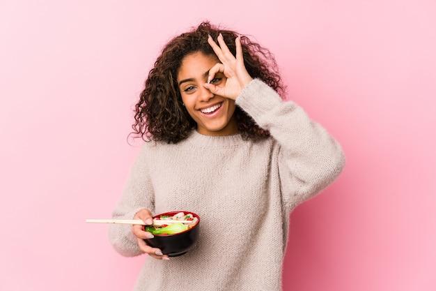 Die junge afroamerikanerfrau, die nudeln isst, regte das halten der okaygeste auf auge auf.
