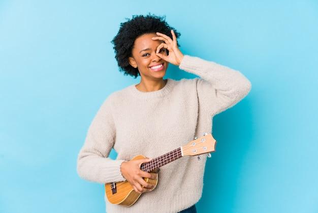 Die junge afroamerikanerfrau, die ukelele spielt, lokalisierte das aufgeregte halten der okaygeste auf auge.