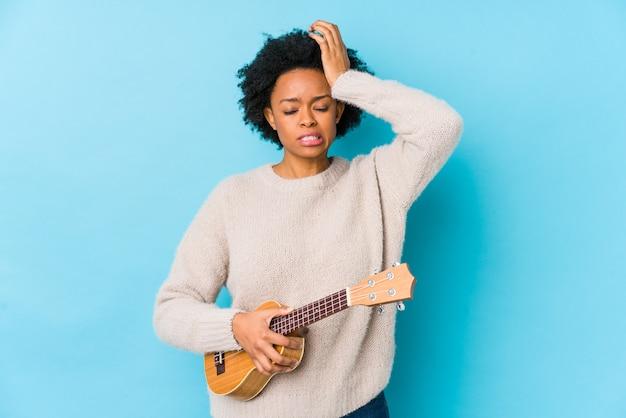 Die junge afroamerikanerfrau, die ukelele spielt, lokalisierte entsetzt seiend, sie hat sich an wichtige sitzung erinnert.