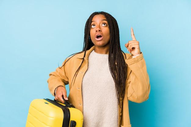 Die junge afroamerikanerreisendfrau, die einen koffer hält, lokalisierte das zeigen der oberseite mit geöffnetem mund.