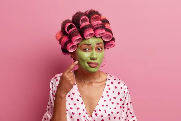 Die junge afroamerikanische frau zeigt auf das gesicht, zeigt, wie sie sich um die haut kümmert, trägt eine grüne maske auf, wartet auf den verjüngungseffekt, trägt lockenwickler auf, bereitet sich auf die party vor, trägt eine lässige robe und posiert im innenbereich