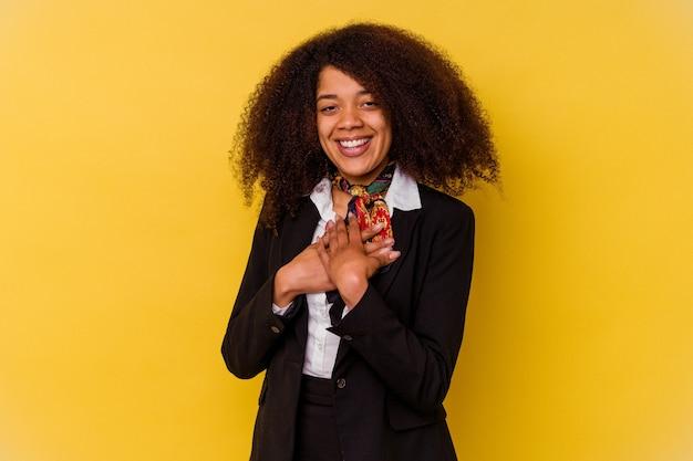 Die junge afroamerikanische stewardess, die auf gelb isoliert ist, hat einen freundlichen ausdruck und drückt die handfläche auf die brust. liebe konzept.