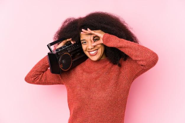 Die junge afrofrau, die eine kassette hält, lokalisierte aufgeregt, okaygeste auf auge halten.