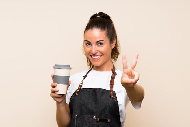 Die junge angestelltfrau, die ein hält, nehmen den kaffee weg, der siegeszeichen lächelt und zeigt