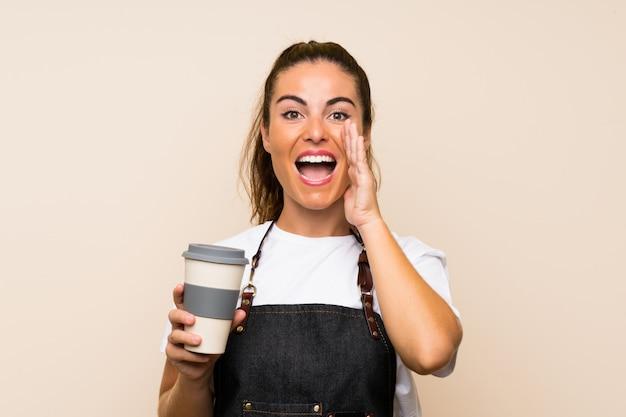 Die junge angestelltfrau, die einen mitnehmerkaffee schreit mit dem breiten mund hält, öffnen sich