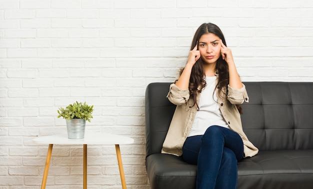 Die junge arabische frau, die auf dem sofa sitzt, konzentrierte sich auf eine aufgabe und hielt die zeigefinger, die kopf zeigen.