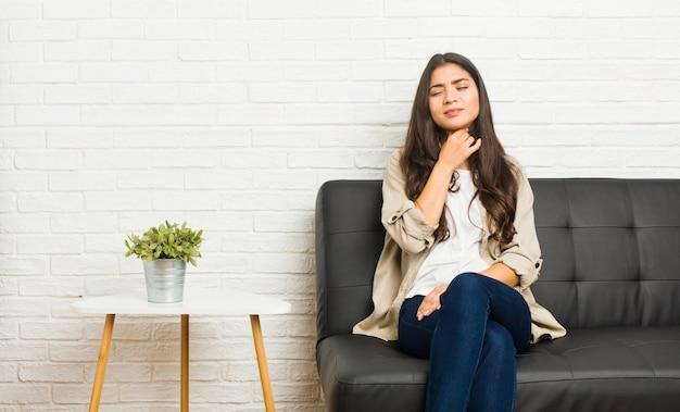 Die junge arabische frau, die auf dem sofa sitzt, leidet die schmerz in der kehle wegen eines virus oder einer infektion.