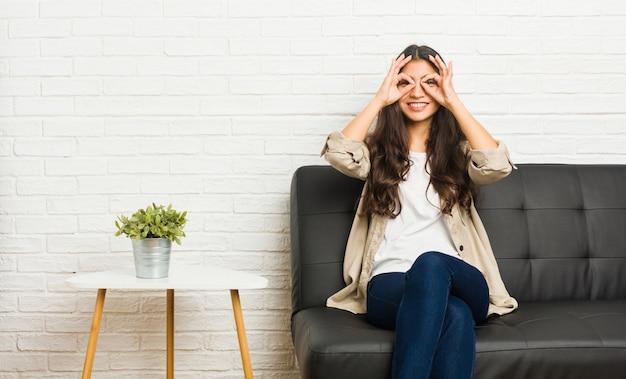 Die junge arabische frau, die auf dem sofa zeigt okay sitzt, unterzeichnen vorbei augen