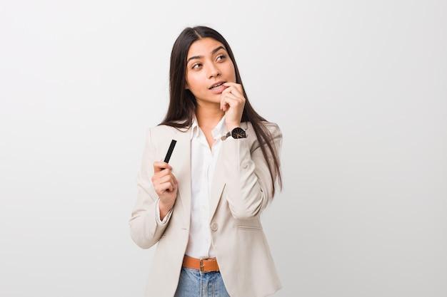 Die junge arabische frau, die eine kreditkarte hält, entspannte sich das denken an etwas, das a betrachtet.