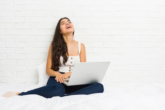Die junge arabische frau, die mit ihrem laptop auf dem bett arbeitet, entspannte sich und das glückliche lachen, der ausgedehnte hals, der zähne zeigt.