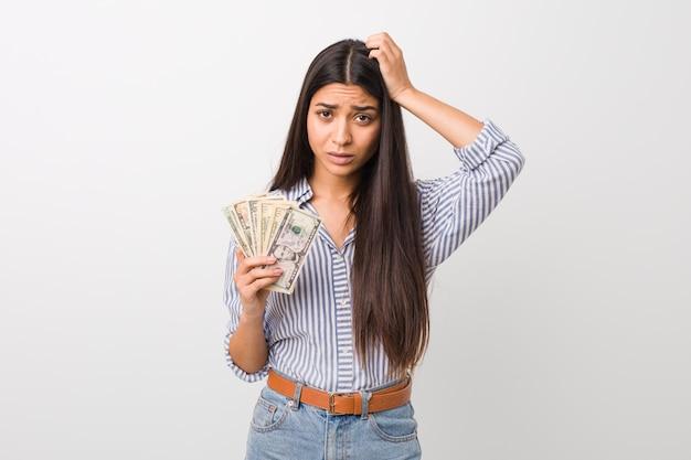 Die junge arabische frau, welche die dollar sind entsetzt anhält, hat sich an wichtige sitzung erinnert.