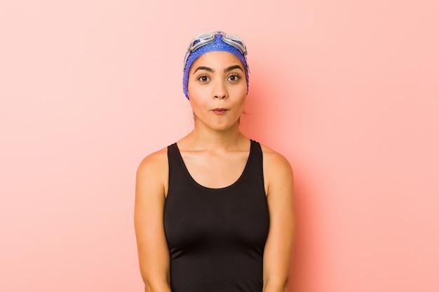 Die junge arabische lokalisierte schwimmerfrau zuckt die schultern und die offenen augen, die verwirrt werden.