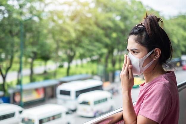 Die junge asiatin, die atemmaske trägt, schützen sich und filtern