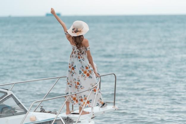 Die junge asiatin, die auf der front des bootsdecks steht, hob arm oben an und untersuchte eine breite seeansicht mit dem langen haar des winds.