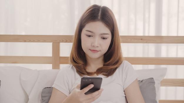 Die junge asiatin, die smartphone verwendet, beim morgens liegen auf bett nach aufwachen