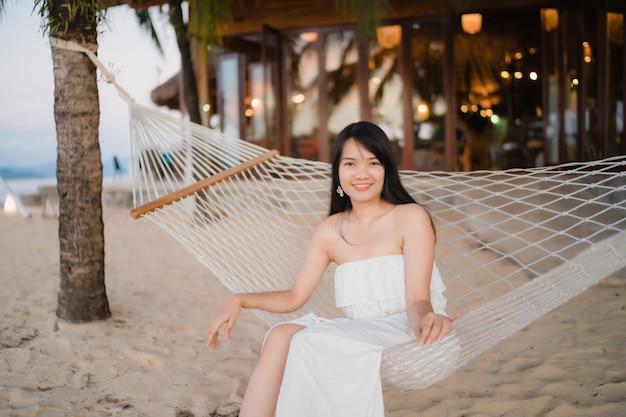 Die junge asiatische frau, die auf hängematte sitzt, entspannen sich auf strand, schönes weibliches glückliches sich entspannen nahe meer.