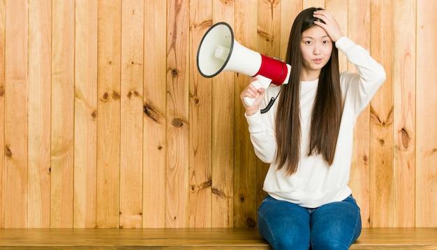 Die junge asiatische frau, die ein megaphon entsetzt hält, hat sich an wichtige sitzung erinnert.