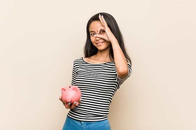 Die junge asiatische frau, die ein sparschwein hält, regte das halten der okaygeste auf auge auf.