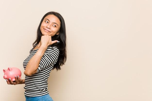 Die junge asiatische frau, die ein sparschwein hält, zeigt mit dem daumenfinger weg, lacht und sorglos.