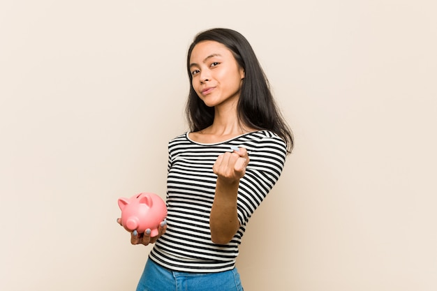 Die junge asiatische frau, die ein sparschwein zeigt mit dem finger auf sie hält, als ob einladung näher kommen.