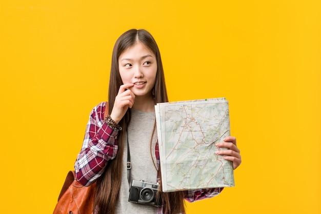 Die junge asiatische frau, die eine karte hält, entspannte sich das denken an etwas