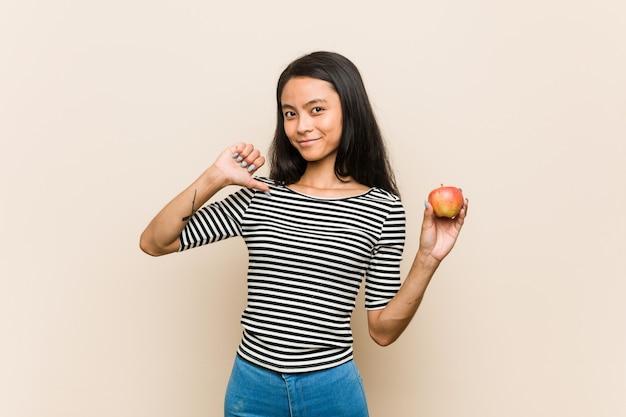 Die junge asiatische frau, die einen apfel hält, fühlt sich stolz und selbstbewusst, beispiel zu folgen.