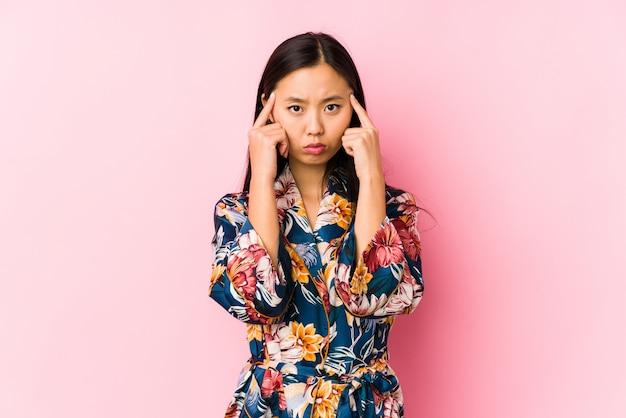 Die junge asiatische frau, die einen kimono-pyjama trägt, konzentrierte sich auf eine aufgabe und hielt die zeigefinger, die kopf zeigen
