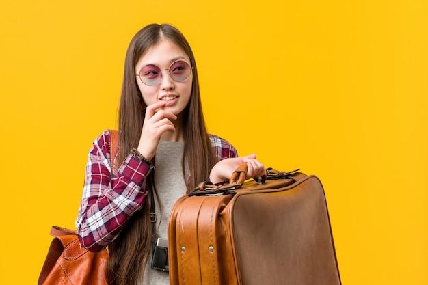 Die junge asiatische frau, die einen koffer hält, entspannte sich das denken an etwas, das einen kopienraum betrachtet.