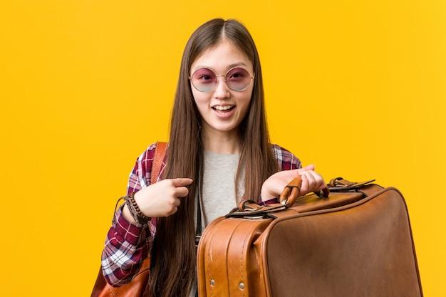 Die junge asiatische frau, die einen koffer hält, überraschte das zeigen auf und breit lächelte.
