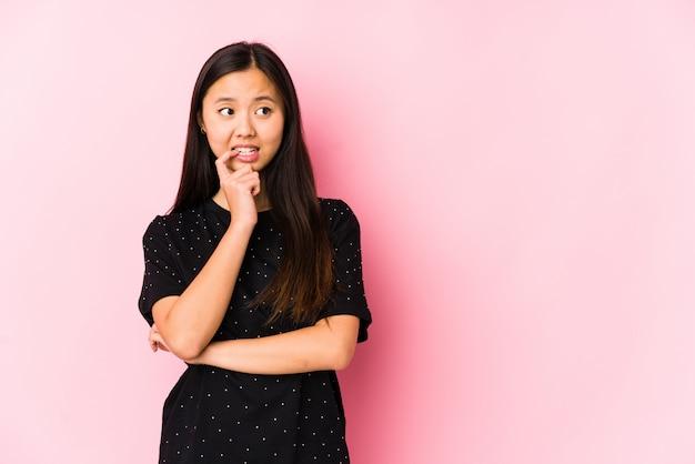 Die junge asiatische frau, die elegante kleidung trägt, lokalisierte das entspannte denken an etwas, das einen kopienraum betrachtet.