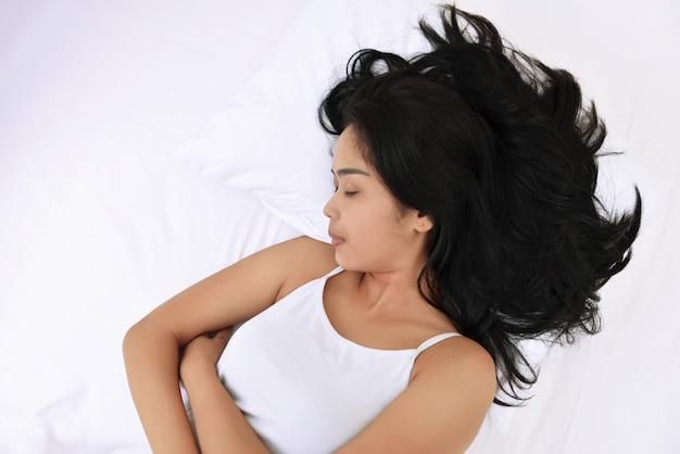 Die junge asiatische frau, die mit schläft, entspannen sich